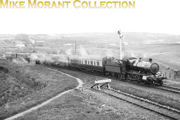 This shot of an unidentified GWR Churchward 4300 class mogul dates from circa 1925 and shows the Penzance portion of the down Cornish Riviera Express approaching Marazion at the end of the single line section from St Erth. This section wasn't doubled until June 1929; (the final section of the Cornish main line, Scorrier to Redruth, wasn't doubled until April 1930). The view is from the bridge over the line at the east end of the station with Marazion Marsh behind the train & Marazion village in the hazy distance. The coaches are in the 1922 livery which suggests a mid-1920s date. The make-up of the train: Van 3rd, 3rd, Compo, Diner, Van 3rd, all 68/70ft vehicles, exactly matches that specified for the CRE in the GW's official 'Programme of Working of Coaches in Through trains' for the summer of 1925. [E. A. Gurney-Smith / Mike Morant collection] This image created quite a stir because of the puzzle as to the location. The solution came from members of the GWS, the GWR E-List and Mike Roach who kindly set the ball rolling. My (our) grateful thanks are extended to all of the contributors.